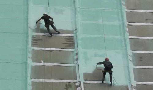 окраска фасада здания альпинистами на страховке